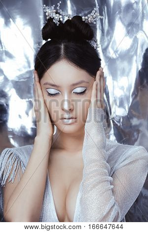 Portrait of futuristic young woman. Reflection of our mind and soul concept. Beautiful young multi-racial asian caucasian model cyber girl in silver urban clothes with conceptual hairstyle and make-up in metallik silver capsule with closed eyes.