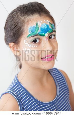 Brunette girl face painted with blue flower on her face