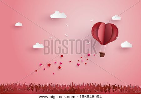 illustration of love and valentine dayOrigami made hot air balloon fly over grass with heart float on the sky.paper art style.