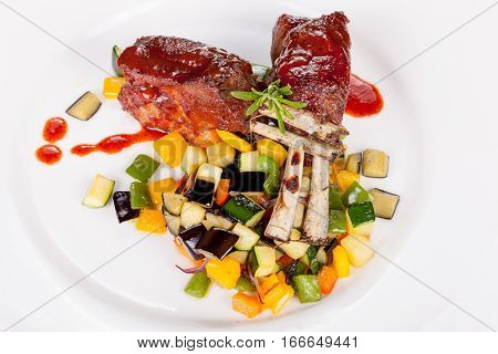 lamb chops with vegetables and sauce on white plate