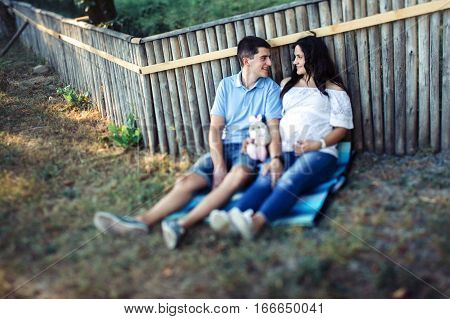 Expecting Couple Rests Under Wooden Fence With Toy Rabbit
