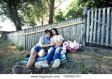 Dreamlike Expecting Couple Sits Under Wooden Fence By Large Basker With Flowers