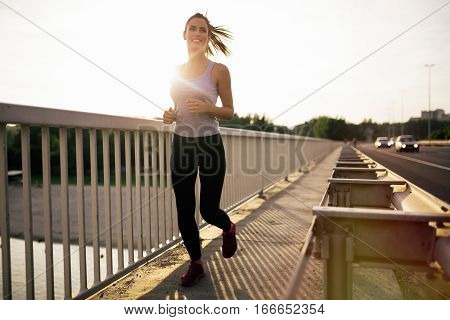 Happy sporty cuteand ypung woman jogging outdoors