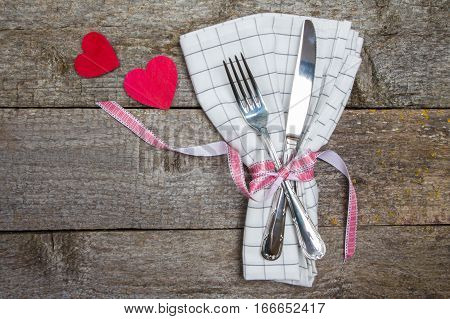 Romantic Dinner: Fork, Knife, Napkin And Hearts On Wooden Table