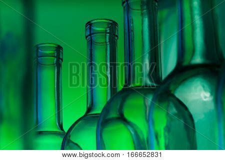 Close-up picture of bottlenecks of empty glass wine bottles on green background