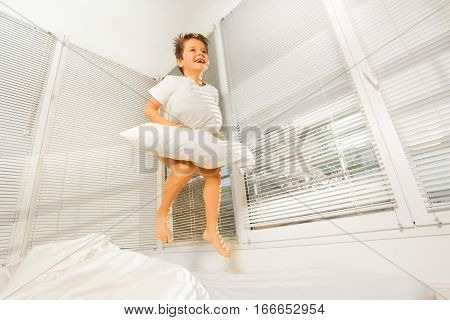 Happy boy jumping on his bad with white pillow in sunny morning