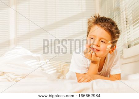 Adorable little boy dreaming in his bedroom laying in bed in morning sun rays