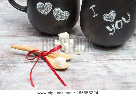 Two Wooden Spoons With Loaf-sugar And Black Tea Mugs
