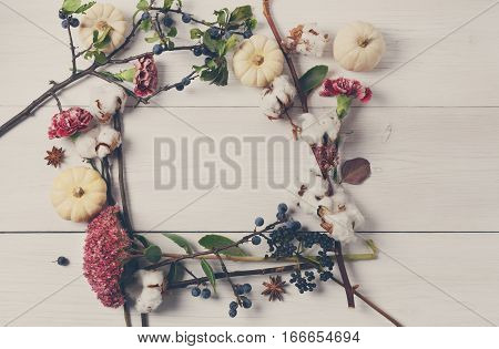 Floral composition. Frame made of dried fall flowers, pumpkins, branches and autumn leaves, also cotton, clove and sloe. Top view on white wood, flat lay, copy space on paper sheet.