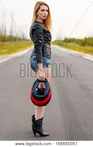 beautiful woman biker standing on the road with a motorcycle helmet in hand