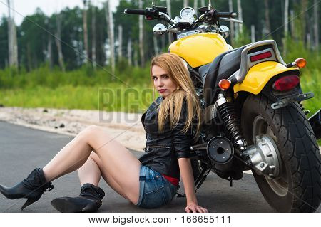 charming sexy woman biker sitting on asphalt with motorcycle