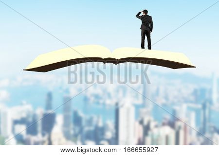 Man standing and gazing on book flying over city buildings background.