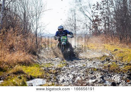 KHABAROVSK RUSSIA - OCTOBER 23 2016: Enduro bike rider on a dirt road. The motorcycle skids and makes a lot of mud splashes