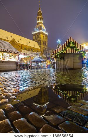RIGA LATVIA - 2nd JAN 2017: Riga Doms Cathedral and Christmas Markets Stalls at Ratslaukums at night in the winter. People can be seen.