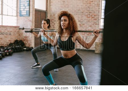 African woman exercising with barbell in fitness class. Females working out in gym with barbell.