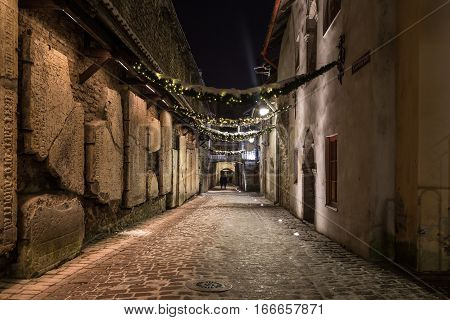 A view along St. Catherine's Passage in Tallinn at night. Tomb Stones can be seen on the left hand side.