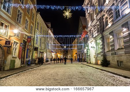 TALLINN ESTONIA - 3RD JAN 2017: A view along Vene Street in Tallinn during the festive months. Decorations buildings and people can be seen.