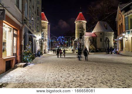 TALLINN ESTONIA - 3RD JAN 2017: A view along Viru Street towards Viru Gate and Towers at night. The blur of people can be seen.
