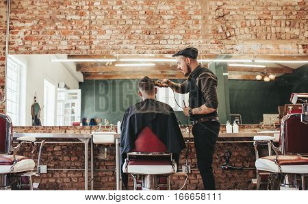 Hairstylist Cutting Hair Of Male Customer