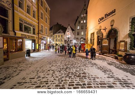 TALLINN ESTONIA - 4TH JAN 2017: A view along streets of Tallinn Old Town at night during the winter. Snow people restaurants and shops can be seen.
