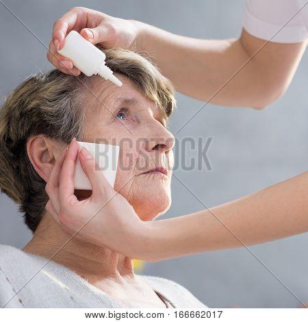 Caregiver Putting Eye Drops