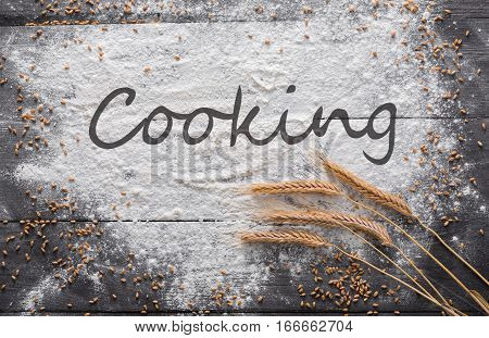 Baking class or recipe concept on dark background, sprinkled wheat flour with cooking text at copy space. Baking preparation, top view on wooden board or table. Making dough or pastry.