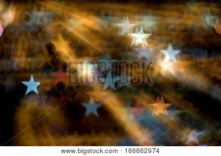 an array of five pointed stars on a dark golden background bokeh effect