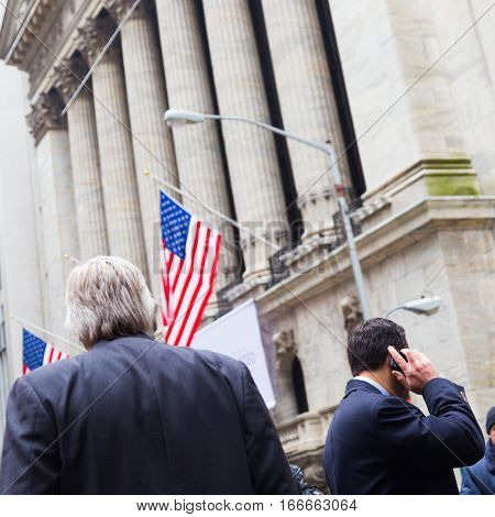 Businessman talking on the phone on Wall street in New York with American flags and New York Stock Exchange in background.