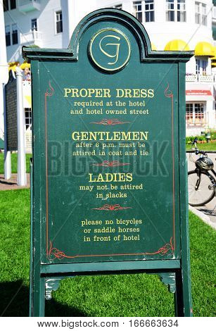 MACKINAC ISLAND - JULY, 2016: A sign posted at the edge of the property shows the dress code required at The Grand Hotel.