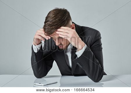 Portrait of attractive young caucasian man using cellular phone while sitting at office table. emotions