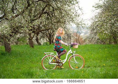 Woman Riding Vintage White Bicycle With Flowers Basket
