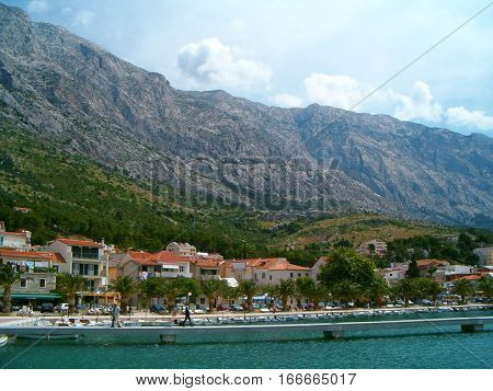 Photo of a seaport in Croatia surrounded by mountains