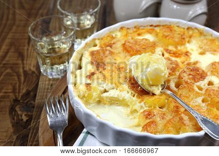 Vegetable potato gratin with cheese and cream in ceramic bakeware