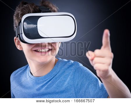 Happy teen boy wearing virtual reality goggles watching movies or playing video games, on black background. Cheerful smiling teenager looking in VR glasses. Funny child experiencing 3D gadget technology.