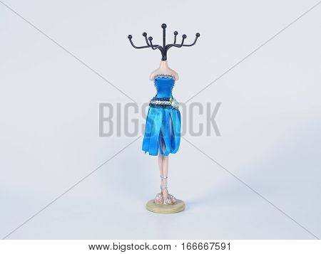 Picture of the bijouterie stay on white background close up. Blue mannequin styled stand for bijouterie.