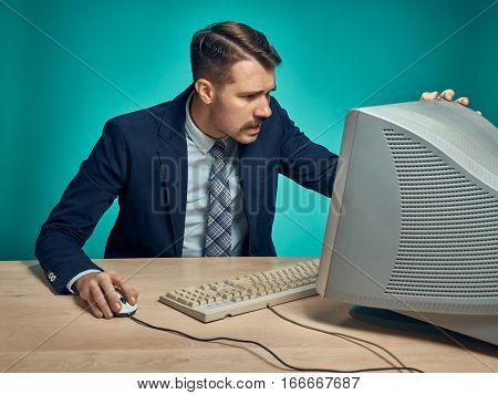 The surprised young man in a business suit working on computer at desk on blue studio background