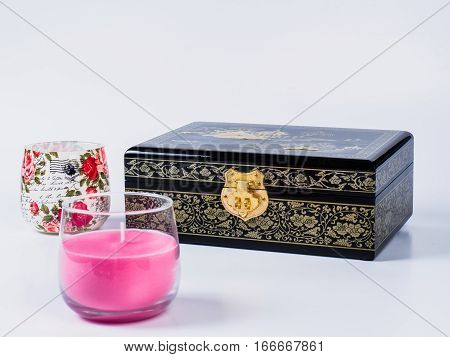 Picture of the wooden jewel-box with painting on wood and golden lock near decoupage glass and pink candle on white background. Painted pattern on closed box for bijouterie. Side view.