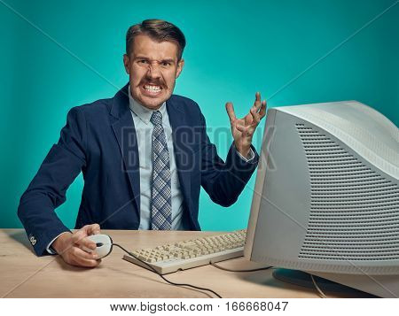 Angry fury businessman using a monitor against a blue studio background poster