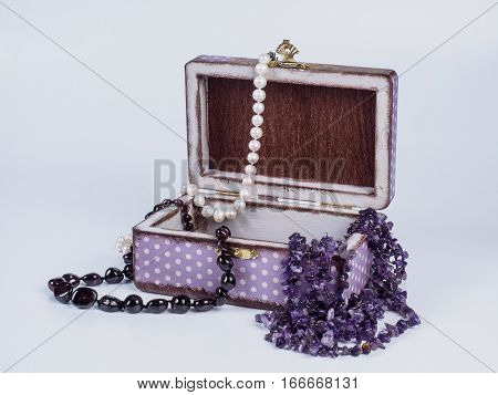 Picture of the opened purple-coloured box for bijouterie with amethyst, pearl and garnet bead necklaces isolated on white background. Handmade decoupage jewel box. Side view.
