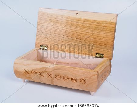 Picture of the carved wooden opened jewel-box for bijouterie on white background. Carved pattern on a jewel box. Closed box made of light wood. Side view.