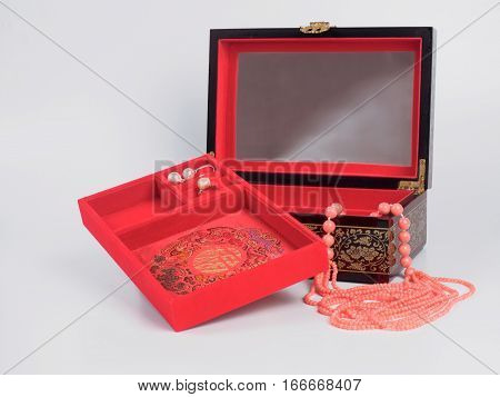 Picture of the opened jewel-box with red fit-out. Wooden jewel-box with pink coral bead necklace on white background. Side view.