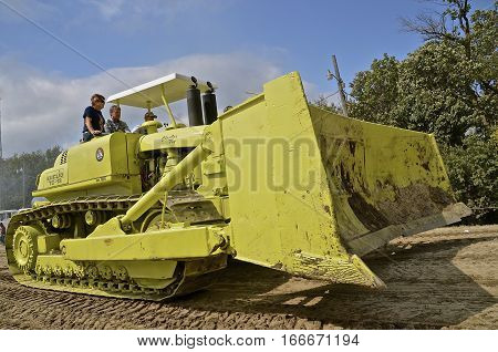 ROLLAG, MINNESOTA, Sept 2, 2016: Two unidentified men operate an old restored Euclid TC-12 bulldozer in a parade at the West Central Steam Threshers Reunion in Rollag, MN attended by 1000's held annually on Labor Day weekend.