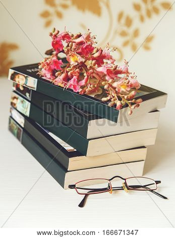 The Branche of Pink Chestnut Tree is on the Pile of Book with Glasses on the White Table.Selective Focus