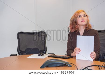 Young business woman shuffling papers and thinking