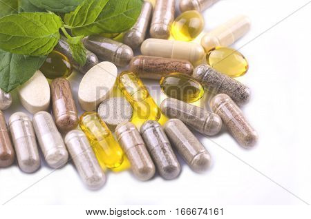 herbal capsules and herbal leaves isolated on white background