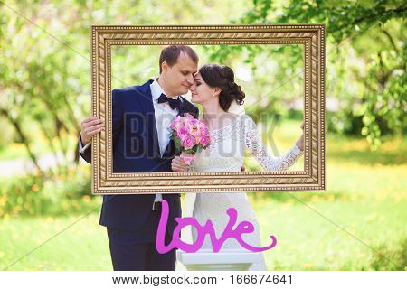 Young newlywed groom and bride with pink wedding bouquet in picture baguette