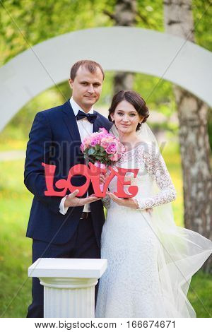 Young newlywed groom and bride with pink wedding bouquet and love word