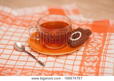 Chocolate cookie in photocamera shape and cup of tea shallow dof