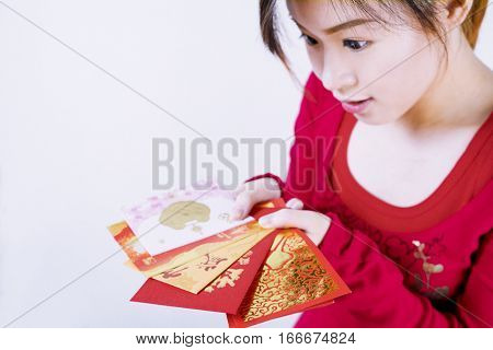 Asian girl look exiting with Red packets in her hands for Chinese New Year Gifts Traditional Celebration Chinese New Year.