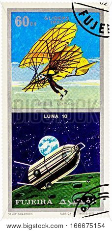 MOSCOW RUSSIA - January 25 2017: A stamp printed in Fujeira shows spacecraft Luna 10 and ancient glider (1852) series